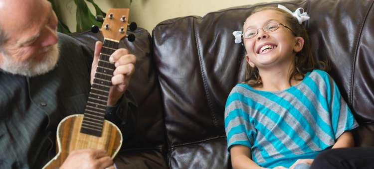 A Smiling girl enjoying an old man's guitar's music