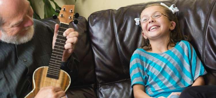 A Smiling girl enjoying an old man's guitar's music