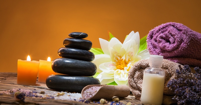 Spa stones, candles, massage oils and flowers arranged for Spa Massage Therapy.