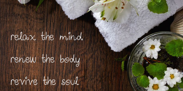 Relax the mind, renew the body and revive the soul text with spa towels and flowers on the table.