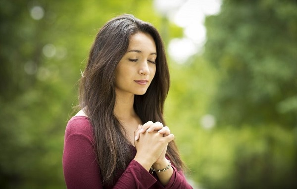 A lady with folded hands praying for the speedy recovery of her loved one.