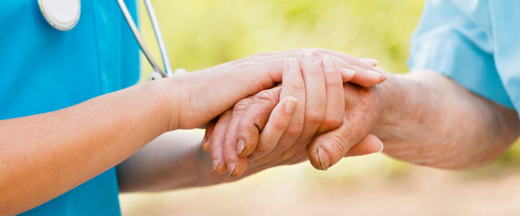 A doctor holding the hands of an elderly patient assuring him of great care.