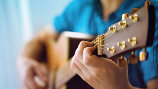 A Man's Hand Holding and playing guitar