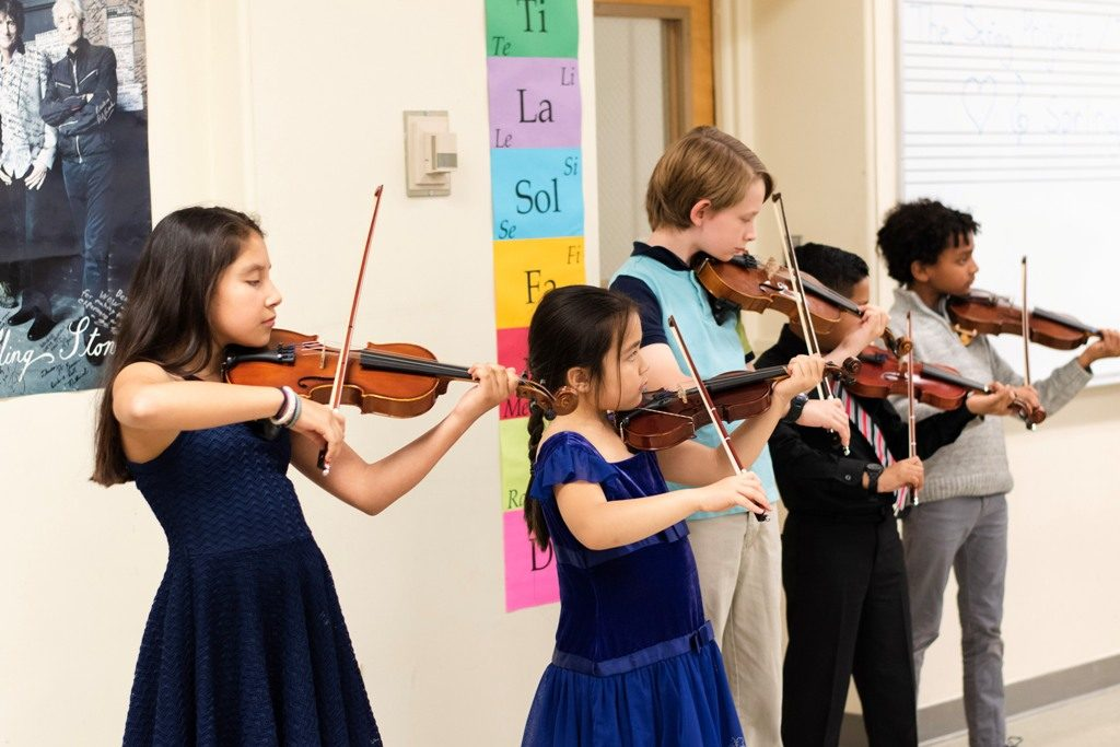 Five kids playing violin in their instrument class