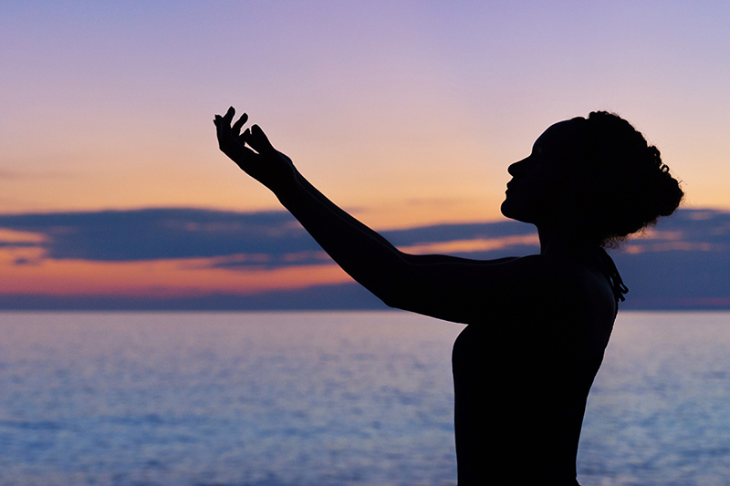 Image showing a woman praying and raising his hands towards sky