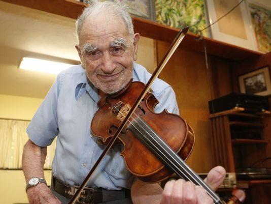 An old man enjoying while playing violin