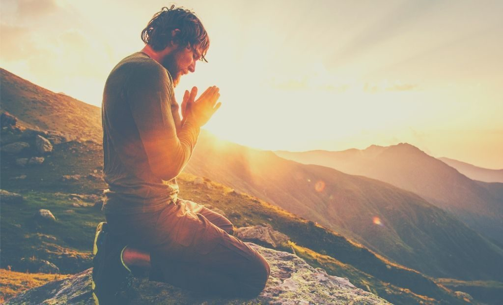 Image showing a man prays from the mountain in a sunset day