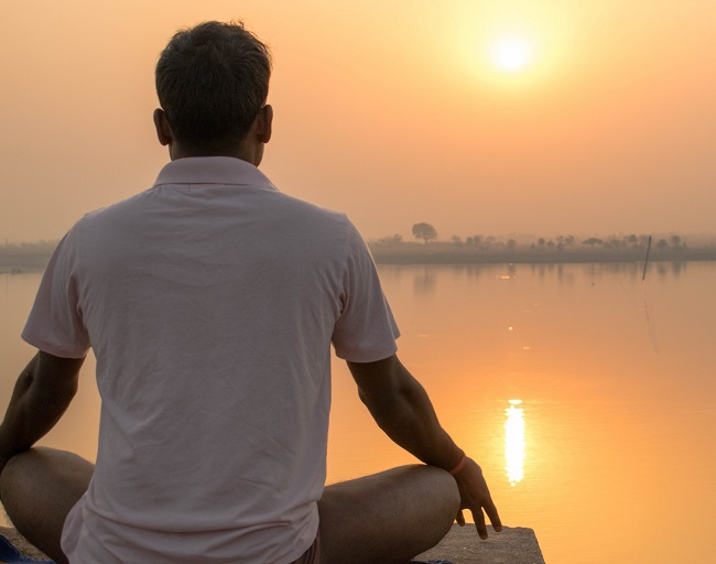 A man practices yoga and meditation in sunrise