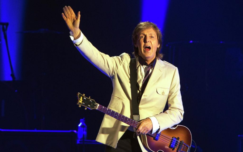 Image shows an old rock singer performing in the stage