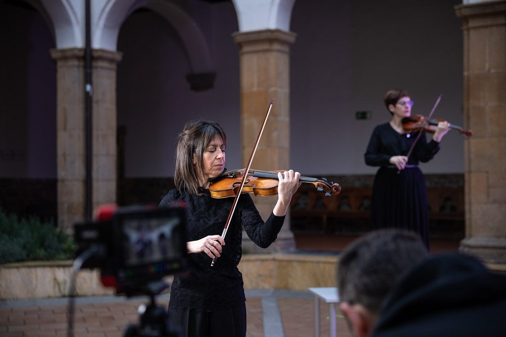 An Old Lady playing violin in a stage performance