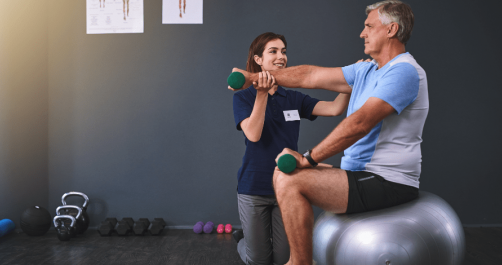 A Senior Man Doing Exercise With The Help Of Health Care Taker.