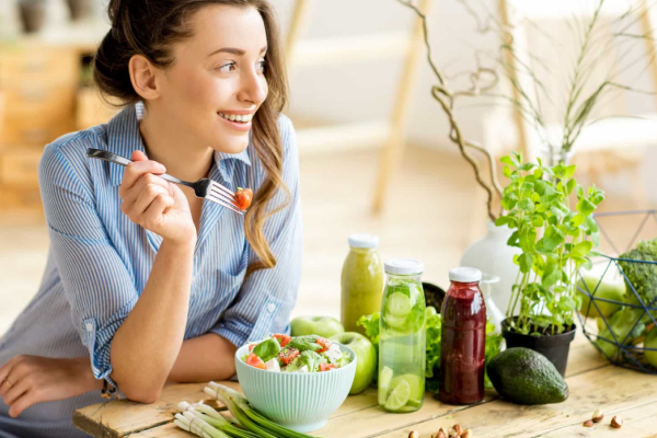 A Happy And Smiling Woman Eating Healthy Food