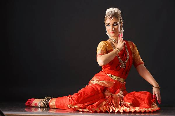:Image of a girl performing Bharatanatyam pose showing Mudras in hand in black background
